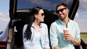 Happy couple with coffee at hatchback car trunk 41. Travel, summer vacation, road trip, leisure and people concept - happy couple drinking coffee from disposable stock video