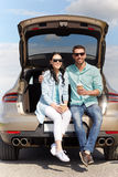 Happy couple with coffee at hatchback car trunk Stock Photos