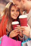 Happy couple with coffee shopping in the mall. A picture of a joyful couple shopping in the mall with coffee Stock Photo