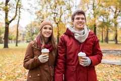 Happy couple with coffee walking in autumn park Royalty Free Stock Images