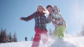 Happy couple in colorful ski costumes. Floor level shooting of joyful young people sliding in the snow towards the