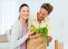 Happy couple coming back from the market stock images