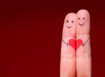 Happy Couple Concept. Two fingers in love with painted smile. Y faces and heart over red background Stock Photos