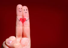 Happy Couple Concept. Two fingers in love with painted smile. Y faces and heart over red background Stock Photography