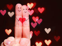 Happy Couple Concept. Two fingers in love. With painted smiley faces and heart over bokeh background Stock Photos