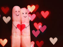Happy Couple Concept. Two fingers in love. With painted smiley faces and heart over bokeh background Stock Images