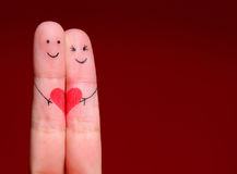 Happy Couple Concept. Two fingers in love. With painted smiley faces and heart over red background stock photography
