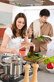 Happy couple cook in kitchen with cookbook Stock Photography