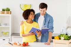 Happy couple with cooking book at home kitchen Stock Photos