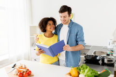 Happy couple with cooking book at home kitchen Royalty Free Stock Photography