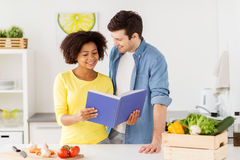 Happy couple with cooking book at home kitchen Stock Photo