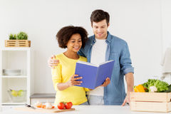 Happy couple with cooking book at home kitchen Royalty Free Stock Photos