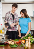 Happy couple cooking with electronic Book in kitchen Stock Photos