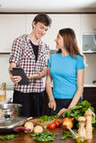 Happy couple cooking with electronic Book in kitchen Royalty Free Stock Image