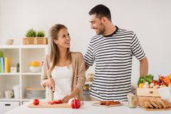 Happy couple cooking food at home kitchen Royalty Free Stock Image