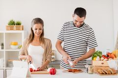 Happy couple cooking food at home kitchen Stock Photo