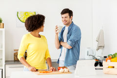 Happy couple cooking food at home kitchen Stock Photos