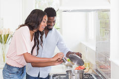 Happy couple cooking food together. At home in the kitchen Stock Image