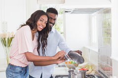 Happy couple cooking food together Stock Photos