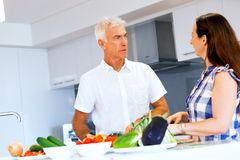 Happy couple cooking at home. Happy mature couple cooking together at home stock photography