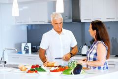 Happy couple cooking at home. Happy mature couple cooking together at home Royalty Free Stock Image