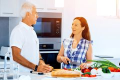 Happy couple cooking at home. Happy mature couple cooking together at home Stock Image