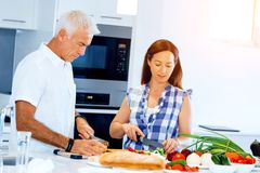 Happy couple cooking at home. Happy mature couple cooking together at home Royalty Free Stock Photos