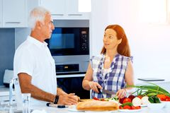 Happy couple cooking at home. Happy mature couple cooking together at home Royalty Free Stock Images