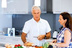 Happy couple cooking at home. Happy mature couple cooking together at home Royalty Free Stock Photo