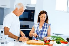 Happy couple cooking at home. Happy mature couple cooking together at home Royalty Free Stock Photography