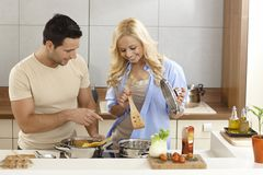 Happy couple cooking in kitchen Royalty Free Stock Images