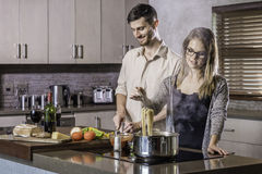 Happy couple cooking a meal in the kitchen flirting bonding Stock Images