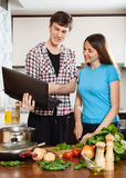 Happy  couple cooking with notebook Stock Photo