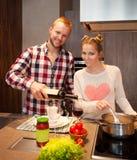 Happy couple cooking pasta Stock Photos