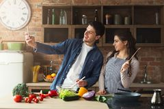 Happy couple cooking and taking selfie in kitchen. Happy couple cooking dinner and taking selfie in their loft kitchen at home. Preparing vegetable salad Stock Images