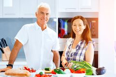 Mature couple cooking at home. Happy couple cooking together at home stock images