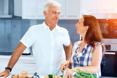 Mature couple cooking at home. Happy couple cooking together at home stock photos