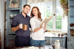 Happy couple cooking together in the kitchen royalty free stock image