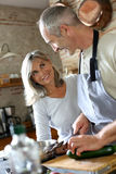 Happy couple cooking together in kitchen Stock Image