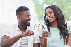 Happy couple on the couch having champagne Stock Photography