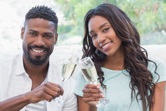 Happy couple on the couch having champagne Royalty Free Stock Image