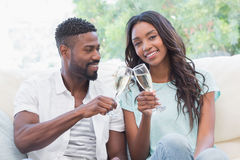 Happy couple on the couch having champagne Royalty Free Stock Photos