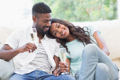 Happy couple on the couch having champagne Stock Image