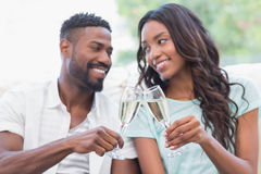 Happy couple on the couch having champagne Stock Photos