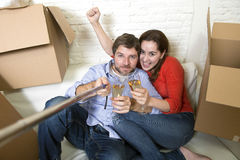 Happy couple on couch having fun together celebrating champagne Royalty Free Stock Photos