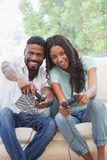 Happy couple on the couch playing video games Stock Images