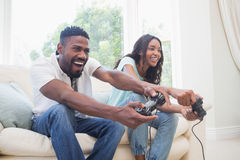 Happy couple on the couch playing video games. At home in the living room Stock Photos