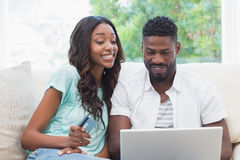 Happy couple on the couch shopping online Stock Images