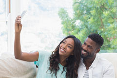 Happy couple on the couch taking selfie Stock Images