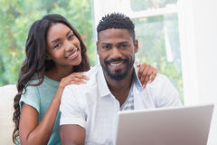 Happy couple on the couch using laptop Royalty Free Stock Photography